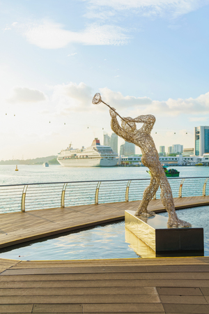 metal sculpture: Singapore - March 1, 2016: Metal Sculpture of Jazz Player and Singapore Cruise Center at Harborfront and Sentosa Boardwalk leading from Mainland Singapore to Sentosa Island.