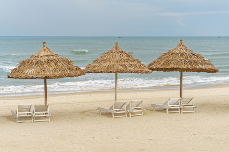 beachfront: Palm shelters and sunbeds on the China Beach in Da Nang, Vietnam. It is also called Non Nuoc Beach. South China Sea on the background.