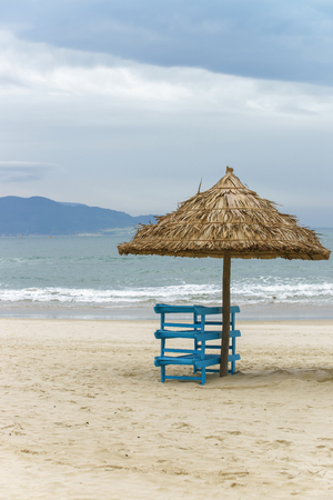 beachfront: Sunbeds and Palm shelter in the China Beach in Da Nang, Vietnam. It is also called Non Nuoc Beach. South China Sea and Marble Mountains on the background.