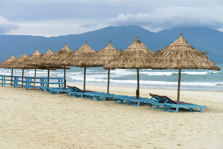 beachfront: Palm shelters and sun beds in the China Beach in Da Nang, in Vietnam. It is also called Non Nuoc Beach. South China Sea and Marble Mountains on the background.