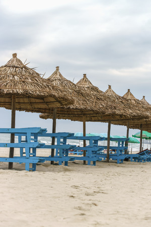Palm shelter and sunbeds in the China Beach in Da Nang, in Vietnam. It is also called Non Nuoc Beach. South China Sea on the background. Stock Photo