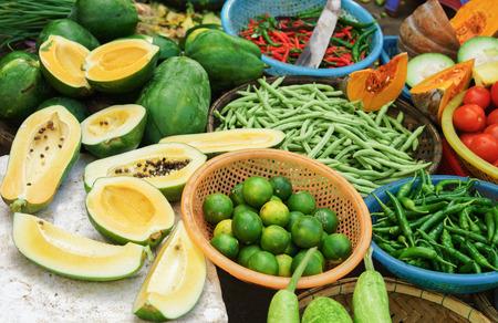 Asiatischer Bauernstraßenmarkt mit frischem Obst und Gemüse in Vietnam. Papaya, Limette und Pfeffer schneiden. Grüne, gelbe und rote Farben.