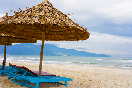 Palm shelters and sunbeds at the China Beach in Da Nang, Vietnam. It is also called Non Nuoc Beach. South China Sea and Marble Mountains on the background.