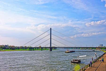 rhine westphalia: Dusseldorf, Germany - May 3, 2013: Oberkasseler Bridge and Rhine embankment promenade in the Old city center in Dusseldorf in Germany. Tourists nearby. It is the capital of Rhine Westphalia region.