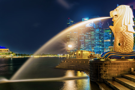 Singapore, Singapore - March 1, 2016: Merlion at Merlion Park at Marina Bay in Singapore at night. Skyline with skyscrapers on the background. Illuminated with light at night