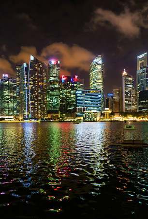 Singapore, Singapore - March 2, 2016: Singapore skyline of Downtown Core on Marina Bay at twilight. Cityscape of famous Skyscrapers illuminated with light and reflected in the water. Editorial