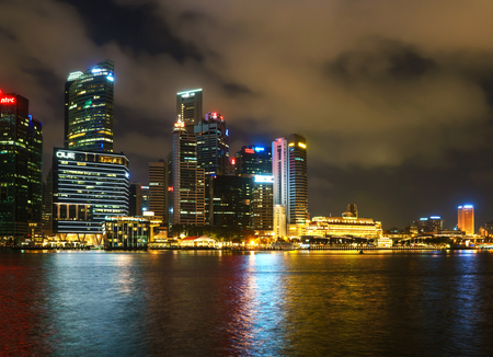 singaporean: Singapore, Singapore - February 29, 2016: Singapore skyline of Downtown Core on Marina Bay at night. Cityscape of famous Skyscrapers illuminated with light and reflected in the water.