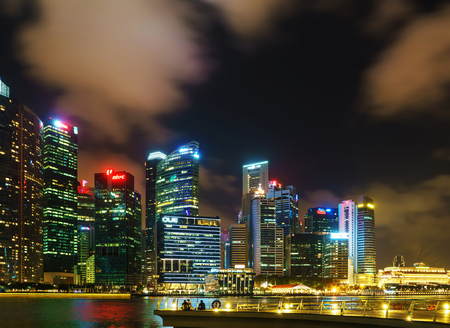 Singapore, Singapore - February 29, 2016: Singapore skyline of Downtown Core on Marina Bay at dusk. Cityscape of famous Skyscrapers illuminated with light and reflected in the water.