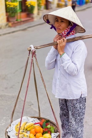 Hoi An, Vietnam - February 16, 2016: Asian trader carrying fresh fruit in bowls on her shoulders in the street in Hoi An, Vietnam. Rambutan, mango, banana and mandarin.