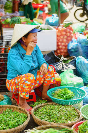 hoi an: Hoi An, Vietnam - February 17, 2016: Asian woman trader selling fresh greens in the street market in Hoi An, Vietnam.