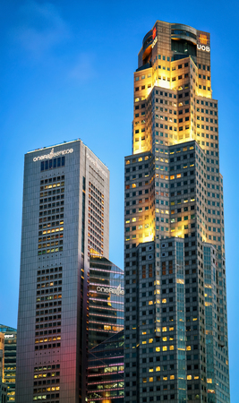 Singapore, Singapore - February 29, 2016: One Raffles Place and UOB Plaza in Downtown Core of Singapore skyline in the evening. United Overseas Bank is located in the Plaza
