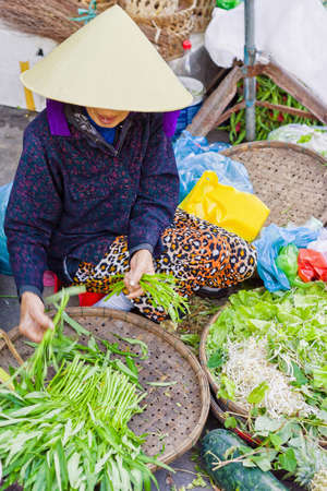 garden stuff: Asian trader in a traditional vietnamese hat selling fresh green garden stuff in the street market in Hoi An, Vietnam. No face. Selective focus