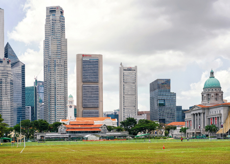 cricket field: Singapore, Singapore - March 1, 2016: Skyline of One Raffles Place and UOB Building with Old Supreme Court and Victoria Theater and concert Hall  in Singapore. View from Padang, former cricket field