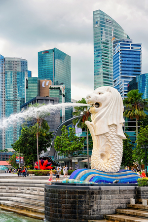 Singapore, Singapore - March 1, 2016: Merlion statue spraying the water from its mouth at Merlion Park in Downtown Core in Singapore at Marina Bay. Skyscrapers on the background.