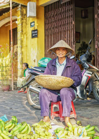 hoi an: Hoi An, Vietnam - February 17, 2016: Asian man in traditional hat selling bunches of bananas in the street market in Hoi An, Vietnam. Editorial