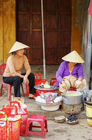 hoi an: Hoi An, Vietnam - February 17, 2016: Asian people in traditional Vietnamese hats cooking food for selling in the street market in Hoi An, Vietnam.