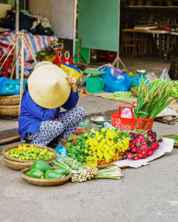 hoi an: Hoi An, Vietnam - February 17, 2016: Asian trader in a traditional vietnamese hat selling fresh flowers, fruit and vegetables on the street market in Hoi An, Vietnam.