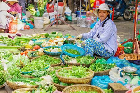 garden stuff: Hoi An, Vietnam - February 17, 2016: Asian trader in a traditional vietnamese hat selling fresh vegetables and green garden stuff in the street market in Hoi An, Vietnam. Editorial