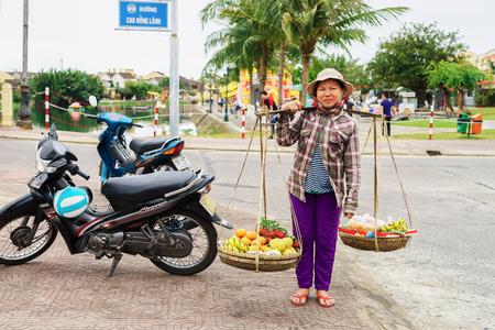 greengrocer: Hoi An, Vietnam - February 16, 2016: Asian woman greengrocer carrying fresh fruit in bowls on her shoulders in the street in Hoi An, Vietnam. Rambutan, mango, banana and mandarin.