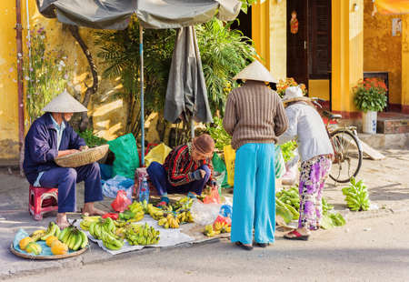 hoi an: Hoi An, Vietnam - February 17, 2016: Asian traders in traditional vietnamese hats selling bunches of fresh bananas in the street market in Hoi An, Vietnam.