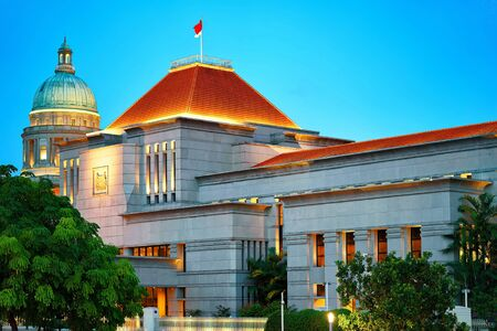 Parliament and Old Supreme Court Building at Boat Quay in Singapore at night. It is illuminated with light.
