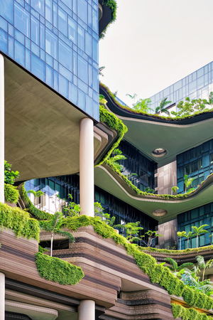 Singapore, Singapore - March 1, 2016: Modern architecture of a balcony of the building with much green plants. Modern design in the center of Singapore.