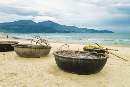 Bamboo waterproof round fishing boat on the China Beach in Danang, in Vietnam. It is also called Non Nuoc Beach. South China Sea and Marble Mountains on the background.