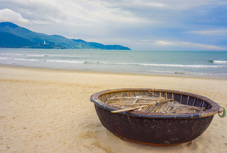 Mountains and Bamboo waterproof round fishing boat at the China Beach in Danang in Vietnam. It is also called Non Nuoc Beach. South China Sea and Marble Mountains on the background. Stock Photo