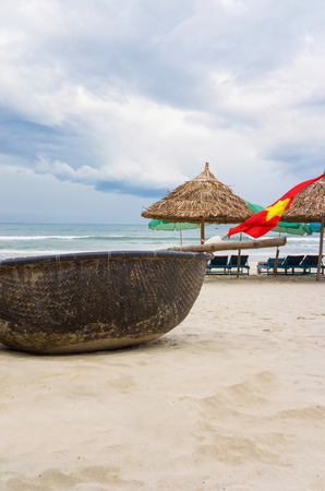 Flag and Bamboo waterproof round fishing boat at the China Beach in Danang in Vietnam. It is also called Non Nuoc Beach. South China Sea and Marble Mountains on the background.