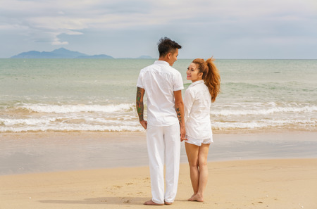 each other: Danang, Vietnam - February 20, 2016: Young couple looking at each other at the China Beach in Danang, in Vietnam