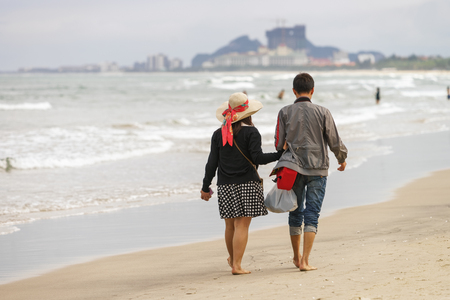 no face: Young couple passing by and holding hands at the China Beach in Danang, in Vietnam. No face