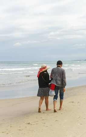 no face: Young couple passing by and holding hands at the China Beach of Danang, in Vietnam. No face