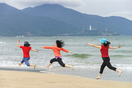 simultaneously: Women trying to jump simultaneously for a good photo at the China Beach in Danang, in Vietnam