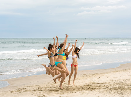 simultaneously: Danang, Vietnam - February 20, 2016: Young girls trying to jump simultaneously for a good photo at the China Beach in Danang, Vietnam Editorial