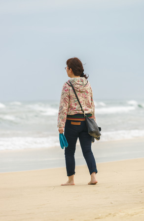 no face: Young girl passing by at the China Beach in Danang, in Vietnam. No face
