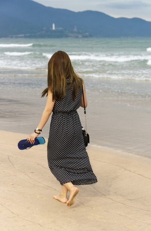 no face: Young girl passing by on the China Beach in Danang, in Vietnam. No face