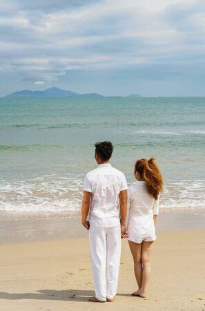beachfront: Young couple standing and looking at the sea at the China Beach of Danang, in Vietnam Stock Photo
