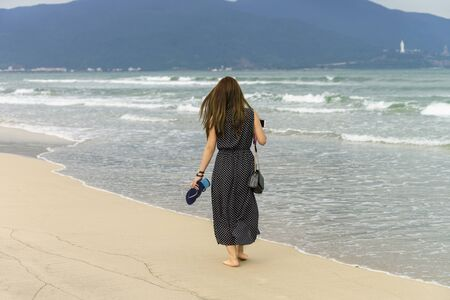 no face: Young girl passing by in the China Beach of Danang, in Vietnam. No face Stock Photo
