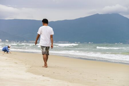 no face: Young man passing by on the China Beach of Danang in Vietnam. No face Stock Photo