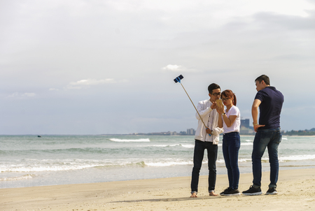 beachfront: Danang, Vietnam - February 20, 2016: Young people use a selfie stick in the China Beach in Danang in Vietnam Editorial