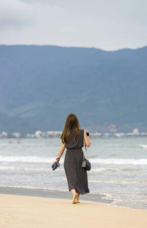 no face: Young girl passing by at the China Beach in Danang,  Vietnam. No face