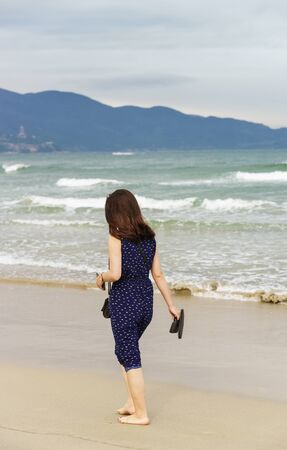no face: Young girl passing by in the China Beach in Danang, Vietnam. No face