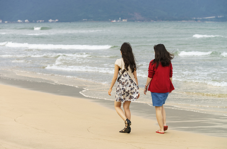 no face: Young girls passing by at the China Beach of Danang in Vietnam. No face Stock Photo