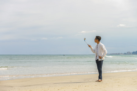 young fellow: Danang, Vietnam - February 20, 2016: Young fellow using a selfie stick in the China Beach in Danang in Vietnam