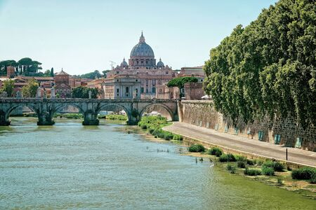 Rome, Italy - August 28, 2012: Dome of Saint Peters Basilica in Vatican city and Ponte Sant Angelo Bridge over the Tiber River in Rome in Italy. Specially toned in vintage style