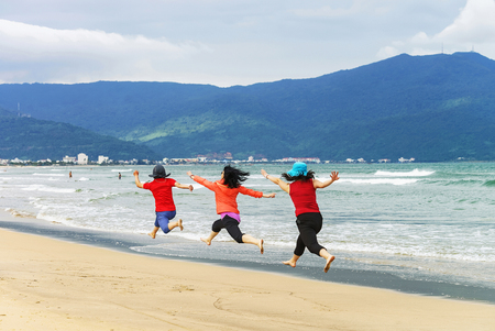 Danang, Vietnam - February 20, 2016: Women trying to jump simultaneously for a good photo at the China Beach of Danang, in Vietnam