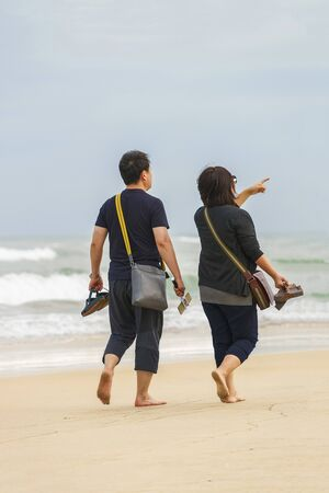 no face: Danang, Vietnam - February 20, 2016: Young couple passing by at the China Beach in Danang, in Vietnam. No face Stock Photo