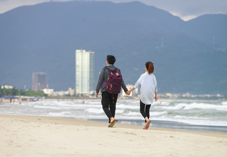 no face: Young couple passing by and holding hands in the China Beach in Danang, in Vietnam. No face