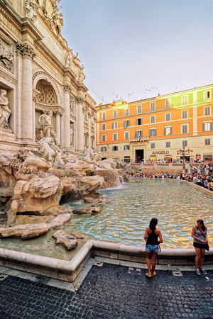 Rome, Italy - August 28, 2012: Travelers at Trevi Fountain in Rome in Italy. It is a fountain in the Trevi district of Rome designed by Nicola Salvi, Italian artist. It is one the most known fountains in the world.