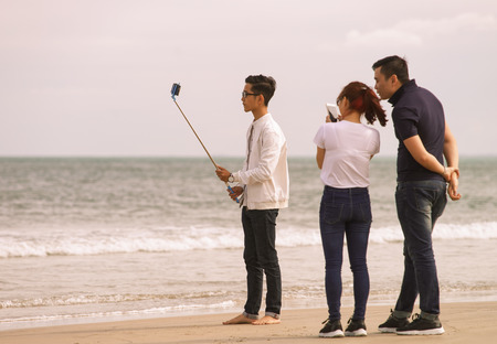 beachfront: Danang, Vietnam - February 20, 2016: Young people using a selfie stick at the China Beach, in Danang in Vietnam